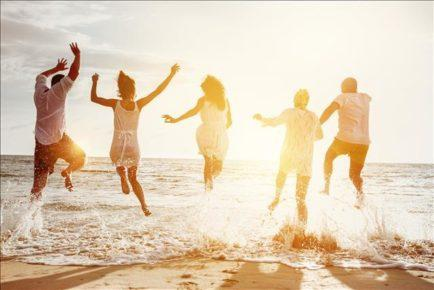 Happy family or friends at the beach running and jumping in the sunset sea